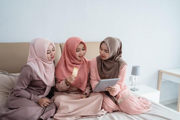 Femmes musulmanes asiatiques utilisant une tablette pour rechercher des articles dans la boutique en ligne lorsque vous restez à la maison