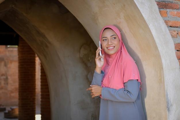 Les femmes musulmanes utilisent les téléphones portables pour contacter les entreprises. a l'ancienne mosquée d'ayutthaya