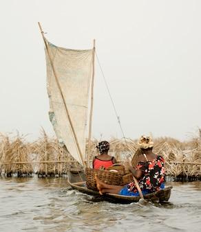 Les femmes de la navigation de plaisance sur la lagune du village sur pilotis ganvie au bénin.