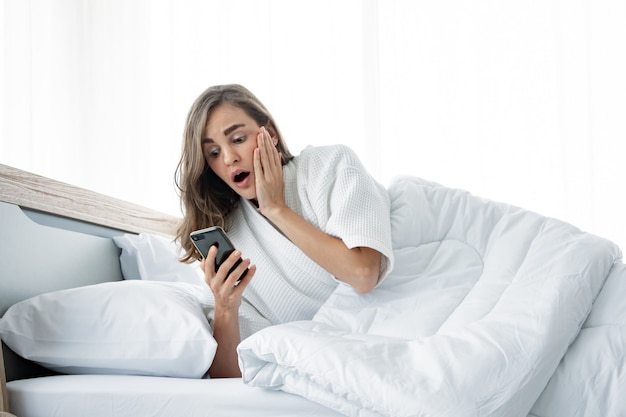 Les femmes ont pris le téléphone avec choc pour apprendre que tard. belle femme en état de choc après son réveil tardif. les femmes se lèvent tard.