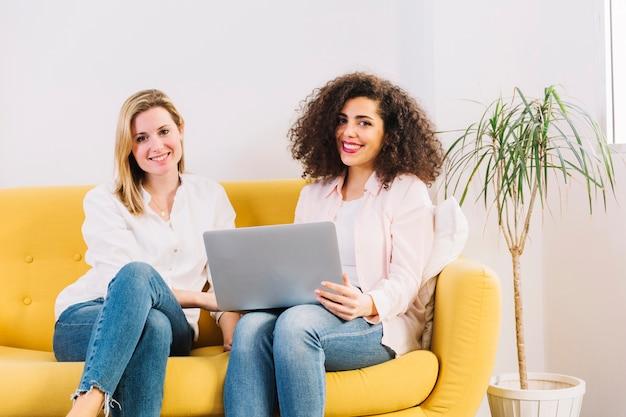 Femmes avec ordinateur portable en regardant la caméra