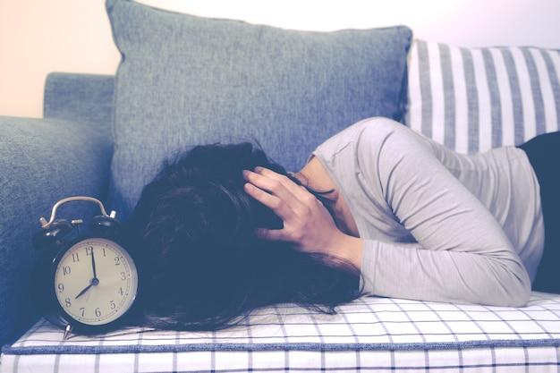 Femmes paresseuses fixant sur le canapé après l'alarme d'horloge, concept réveil tardif