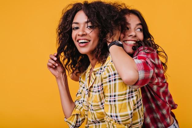 Les femmes à la peau bronzée s'amusent. jolie fille ébouriffant les cheveux de son amie.