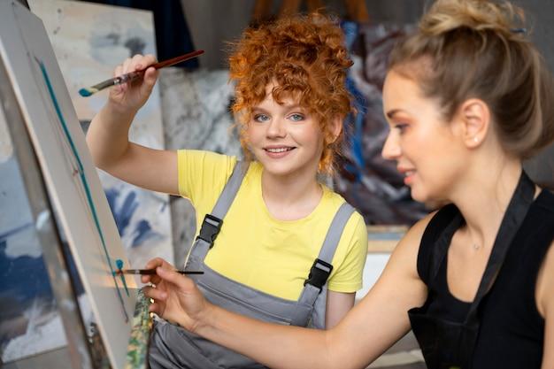 Femmes peignant sur toile en gros plan
