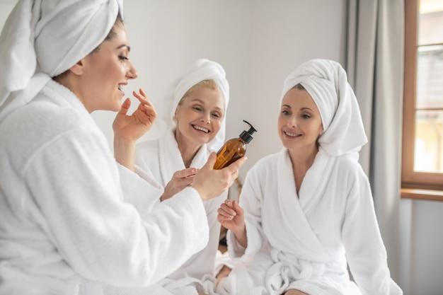 Femmes en peignoirs essayant de nouveaux cosmétiques
