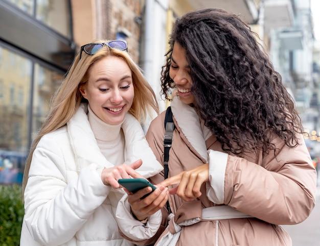 Femmes de plan moyen avec smartphone