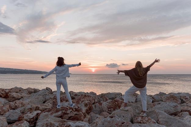 Femmes plein coup au coucher du soleil