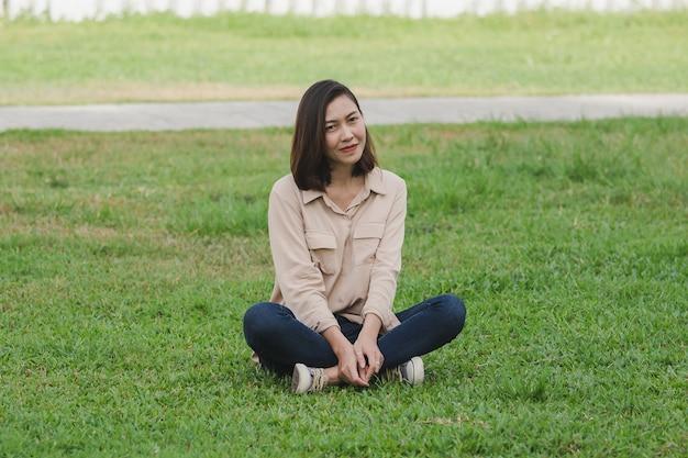 Femmes portant des chemises marron assis sur la pelouse