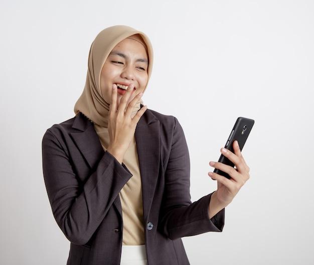 Les femmes portant des costumes hijab rire en regardant le téléphone, concept de travail formel isolé fond blanc