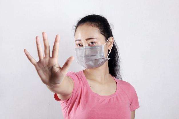 Femmes portant un masque avec geste d'arrêt. arrêtez le coronavirus