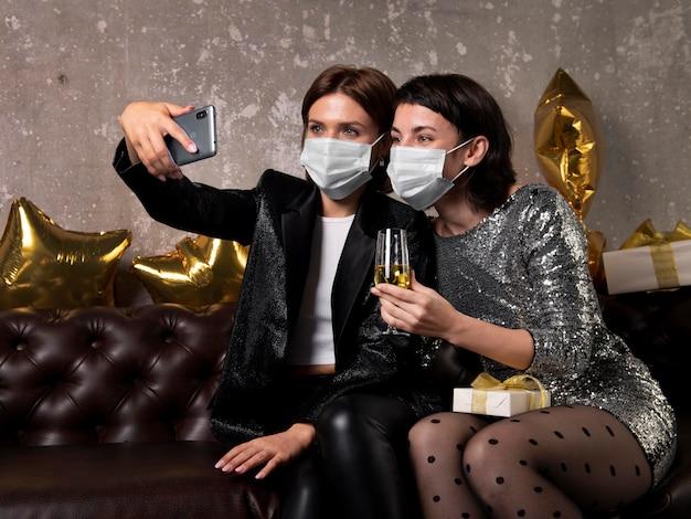 Femmes portant des masques faciaux prenant un selfie