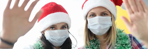 Femmes portant des masques médicaux de protection et des chapeaux de père noël saluant la caméra