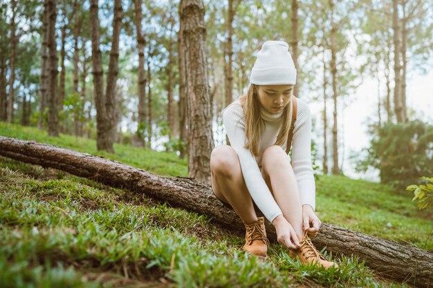 Femmes portant un pull en tricot blanc et une cagoule dans la forêt