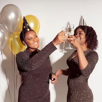 Femmes portant des verres de champagne joyeux anniversaire