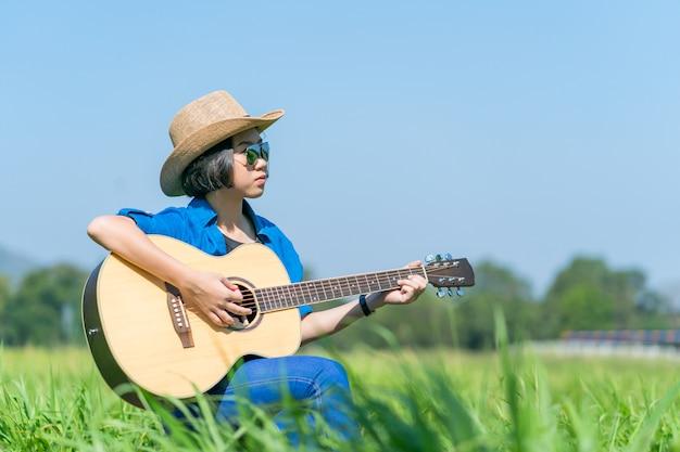 Les femmes portent un chapeau court et des lunettes de soleil s'asseoir jouer de la guitare dans le champ d'herbe