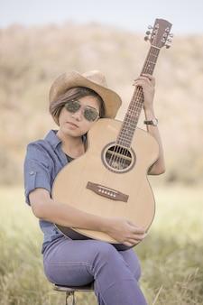 Les femmes portent un chapeau et des lunettes de soleil pour jouer de la guitare dans l'herbe