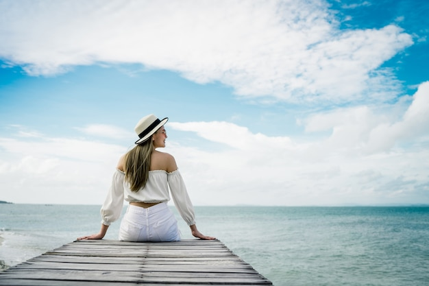 Les femmes portent un chapeau de mer, elle est heureuse et assis sur le pont de bois et se tournent vers la plage de la mer