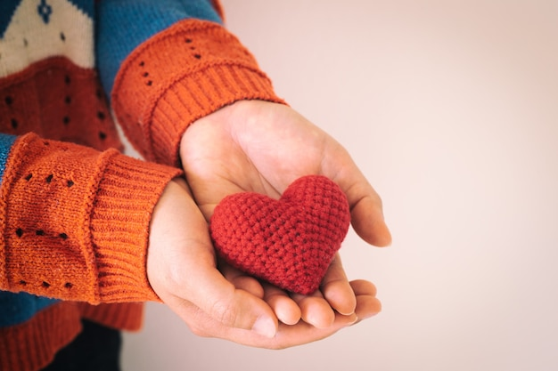 Les femmes portent une chemise en tricot main tenant un coeur rouge.