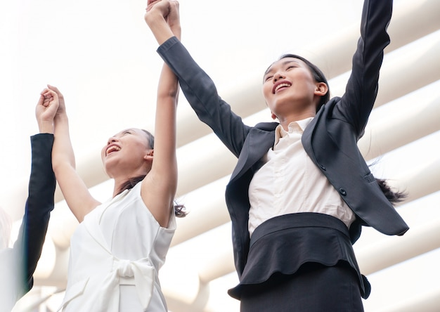 Les femmes portent le costume se lève la main comme projet réussi