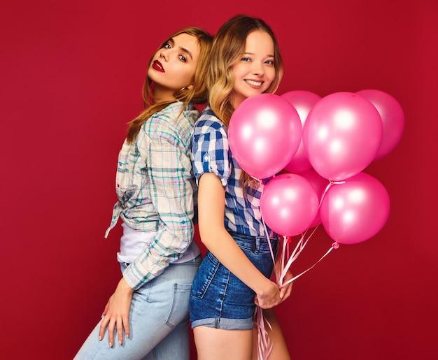 Femmes posant avec une grande boîte-cadeau et des ballons roses