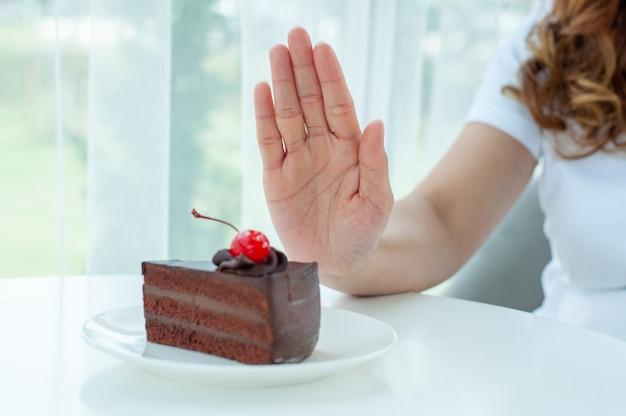 Les femmes poussaient l'assiette à gâteau avec les gens. ne mangez pas de desserts pour perdre du poids.