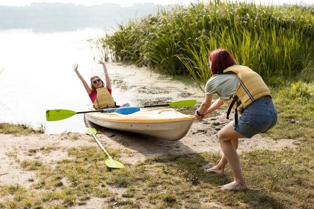 Femmes poussant l'eau d'introduction de kayak