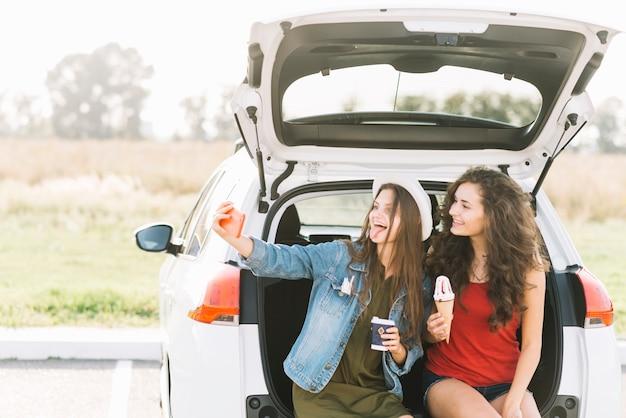 Femmes prenant selfie sur un coffre de voiture