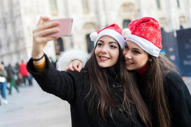 Femmes prenant un selfie lors de leurs achats à milan