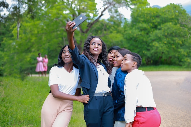 Femmes prenant selfie avec des visages heureux