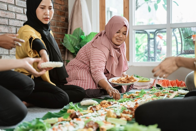 Femmes préparant le dîner avec des amis à la maison