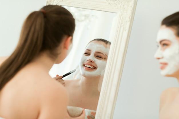 Femmes avec des produits cosmétiques pour le visage