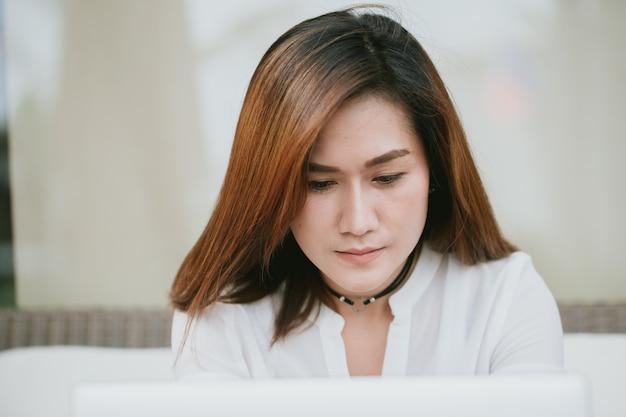 Femmes professionnelles asiatiques travaillent dur en regardant l'écran d'ordinateur portable au bureau