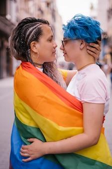 Femmes puissantes gratuites montrant l'amour lesbien sans aucune honte enveloppées dans un drapeau gay.