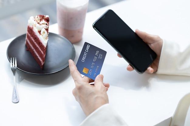 Les femmes qui achètent en ligne par carte de crédit via un smartphone