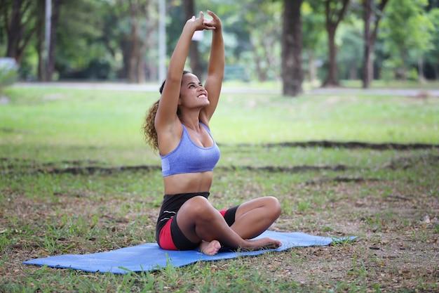 Les femmes de race mixte réchauffent le corps avant le yoga dans le parc