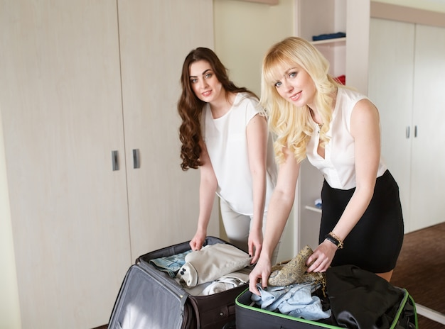 Les femmes ramassent une valise dans une chambre d'hôtel.