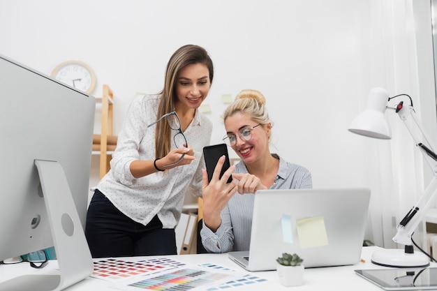 Femmes à la recherche au téléphone au bureau