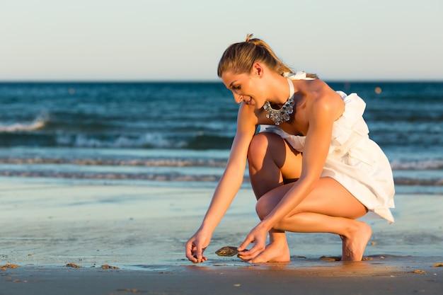 Femmes à la recherche de coquillages au coucher du soleil romantique