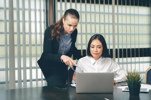 Femmes à la recherche de documents financiers dans un ordinateur portable à table