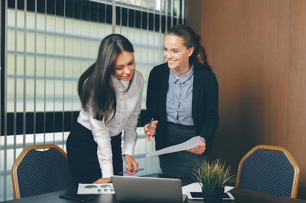 Femmes à la recherche de documents financiers dans un ordinateur portable à la table