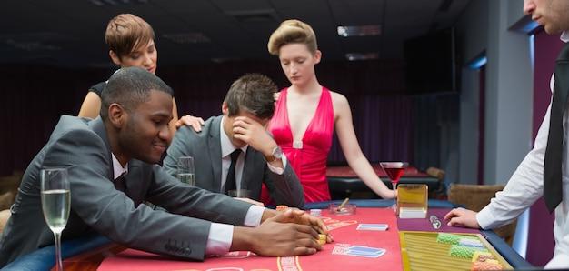 Les femmes réconfortent l'homme comme l'autre homme prend le jackpot