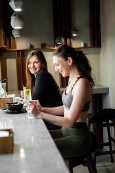 Les femmes refroidissent et boivent une boisson saine après la gym