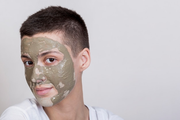 Femmes regardant la caméra avec un traitement de boue sur le visage