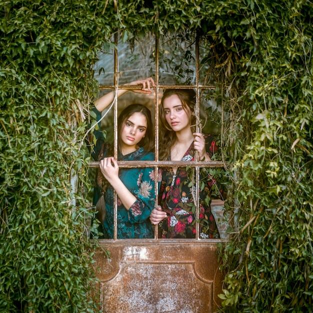 Femmes regardant la caméra à travers les barreaux