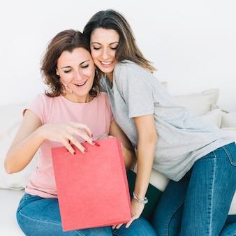 Femmes regardant dans le sac en papier rouge