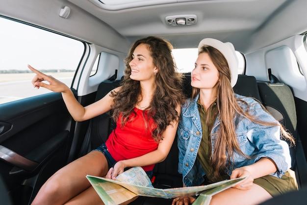 Femmes regardant par la fenêtre de la voiture