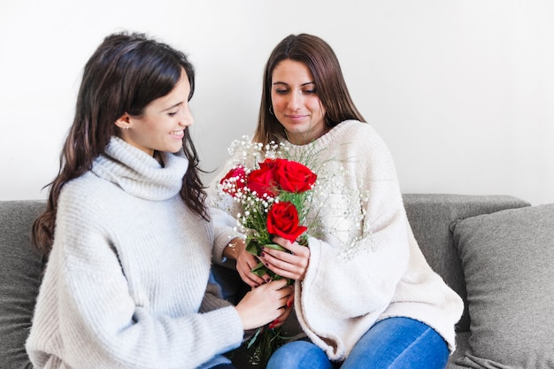 Femmes romantiques donnant des fleurs pour les vacances