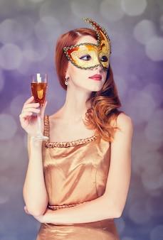 Femmes rousses en masque avec du champagne