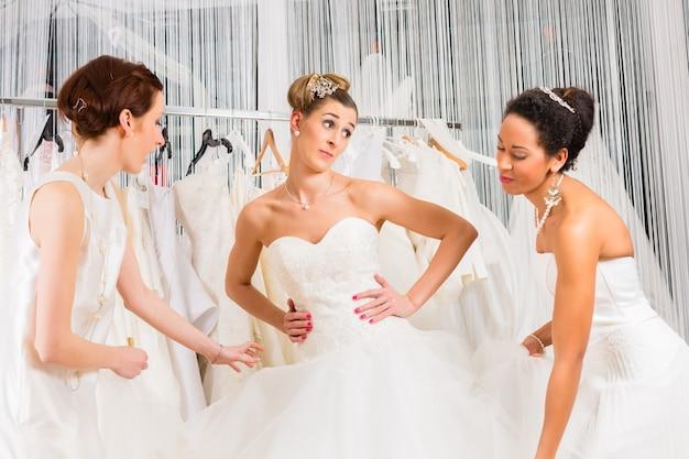 Les femmes s'amusant lors de l'ajustement de la robe de mariée en magasin de mode de mariage