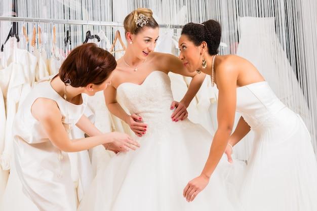 Femmes s'amusant pendant la pose d'une robe de mariée en boutique
